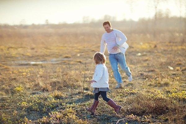 Père et fille s'exécutant sur le terrain gazonné