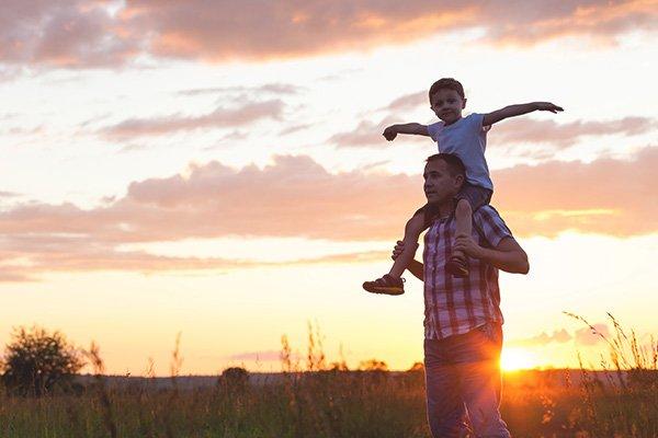 Père portant son fils sur ses épaules avec coucher de soleil derrière eux