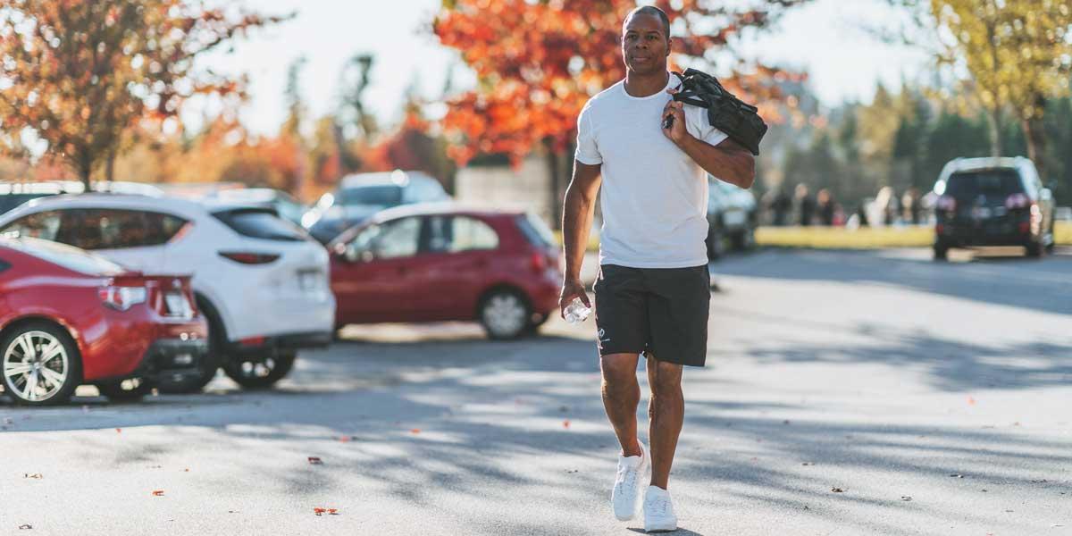 Tommy Europe marchant dans un parking avec un sac