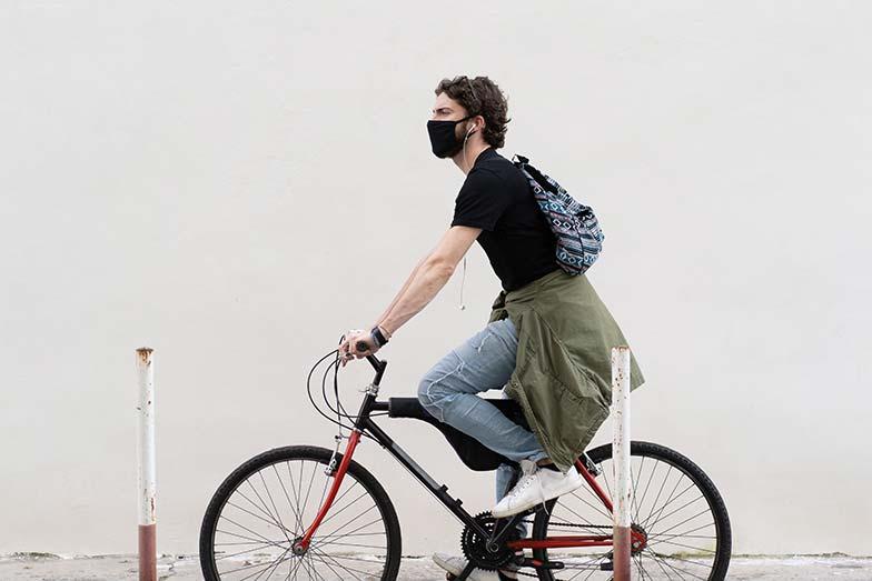 Un jeune homme chevauchant son vélo sans stress et portant un masque au milieu de la pandémie de COVID-19